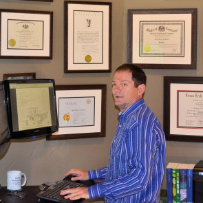 Neal Braswell with his certificates on his office wall
